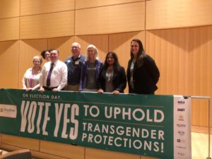"Group smiles and poses with banner that reads ""On Election Day, Vote Yes to Uphold Transgender Protections."""