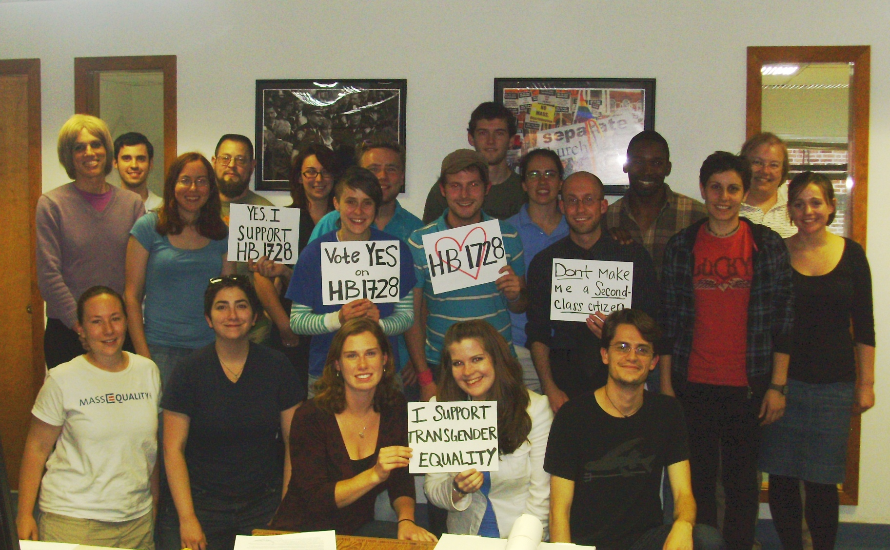 Large group of MassEquality staff and volunteers pose with signs supporting HB1728.