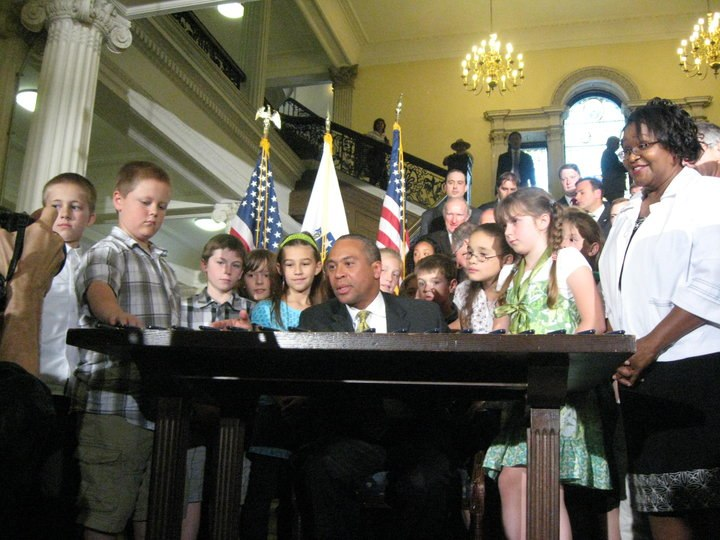 Gov Deval Patrick signs act, surrounded by crowd of mostly children.