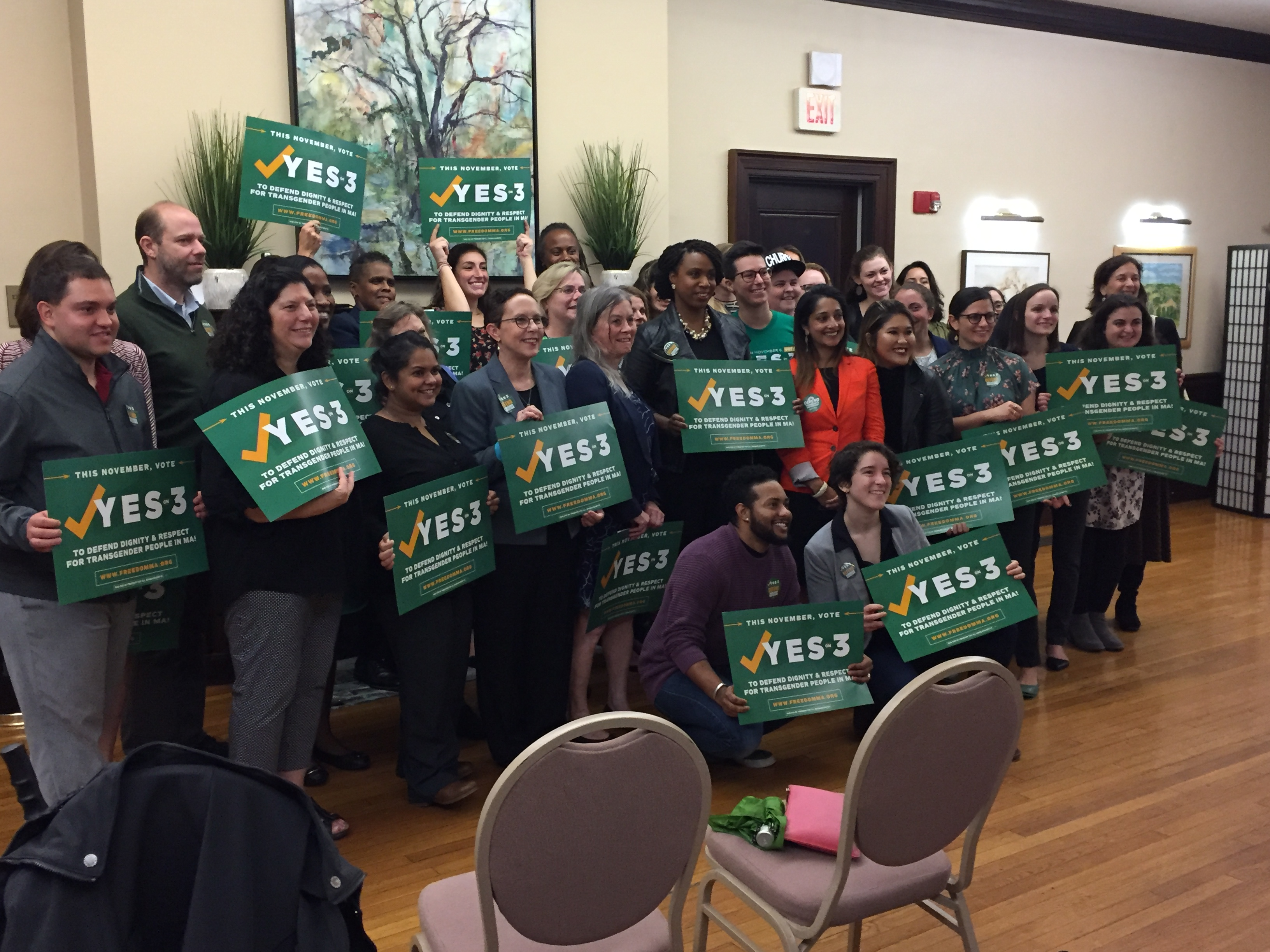 """Rep Ayanna Pressley stands with group of sipporters holding """"Yes on 3"""" signs."""
