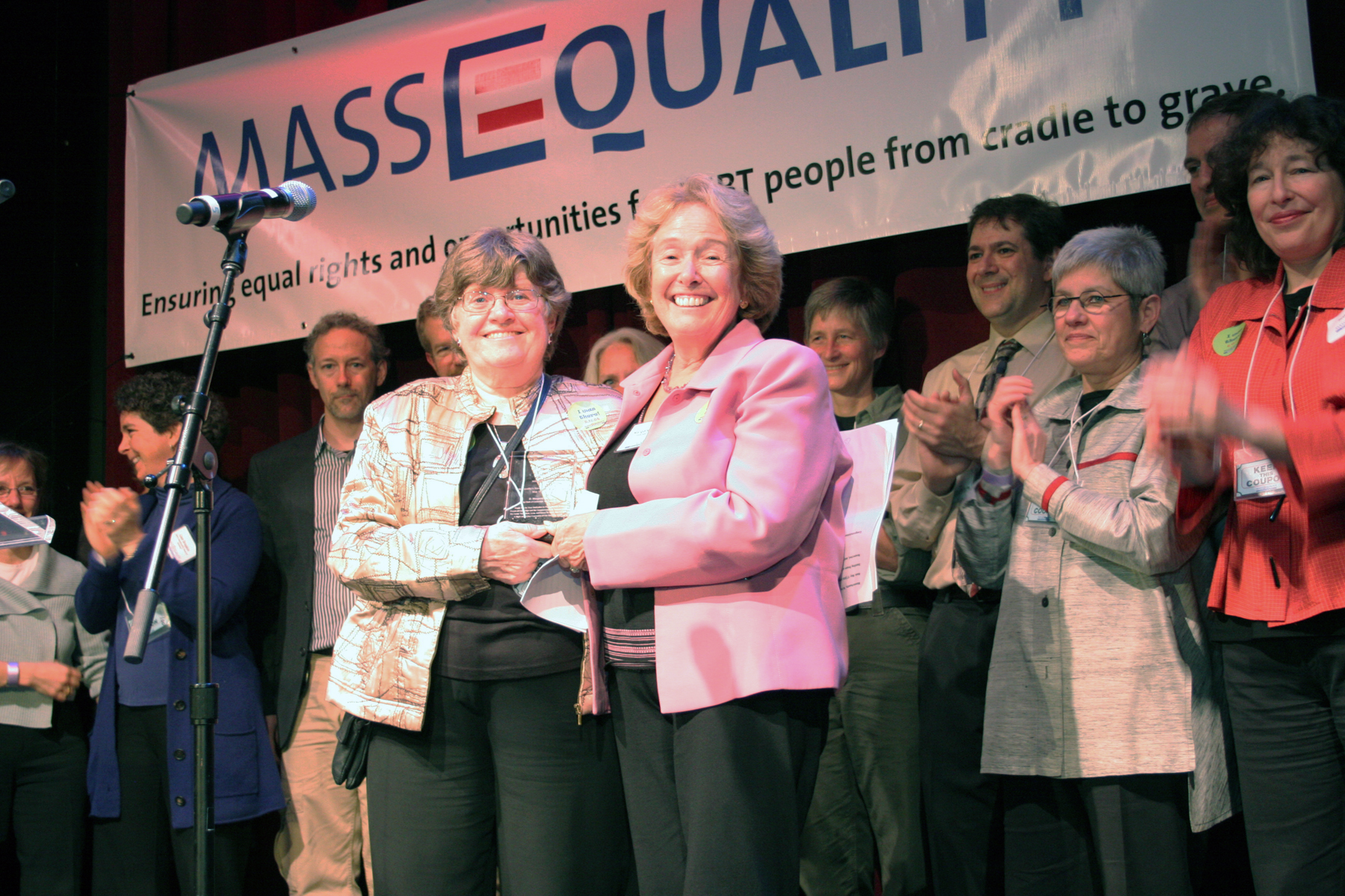 Two women stand on stage holding plaque together in front of MassEquality banner and clapping listeners.
